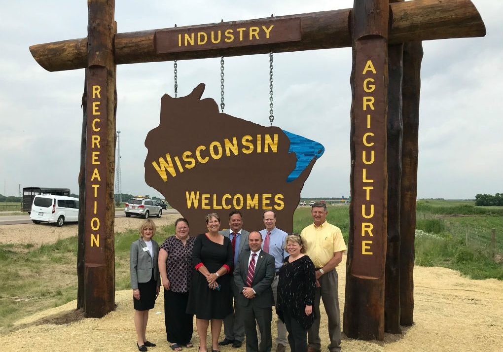 group of people standing in front of wisconsin welcomes you sign on highway