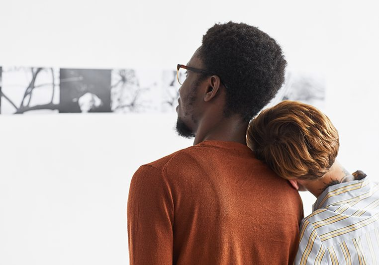 Graphic portrait of mixed-race couple embracing while looking at paintings at modern art gallery exhibition, copy space