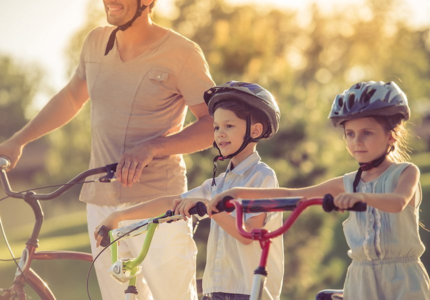 Happy family is riding bikes outdoors, looking forward and smiling