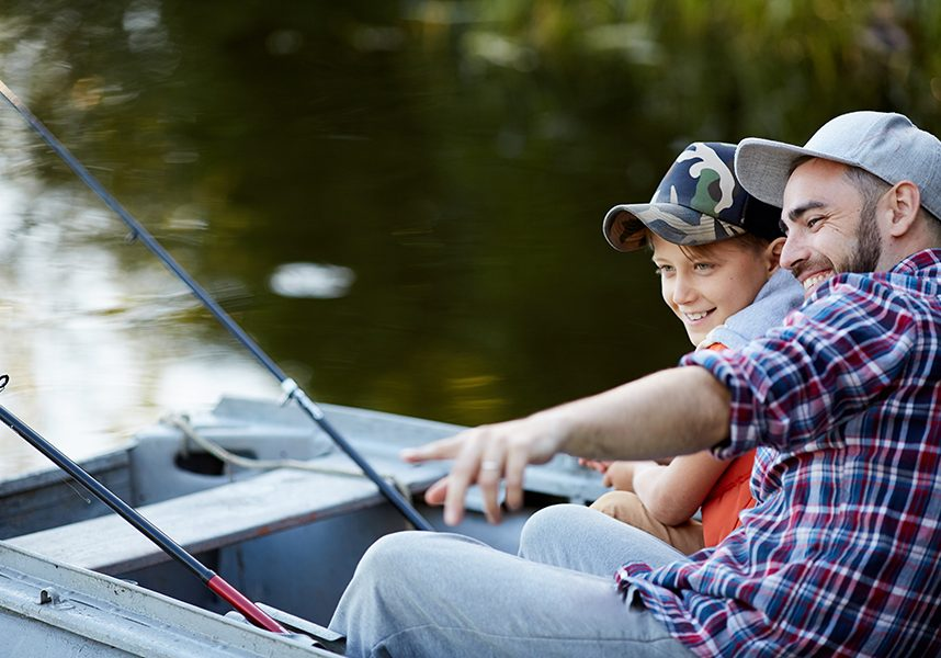 Cheerful father showing to his son a good place for fishing while they sitting in the boat