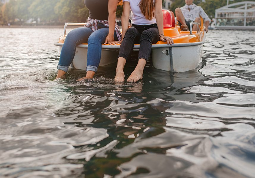 Cropped shot of young women sitting pedal boat front with feet in water. Two young women on a pedalo boat.